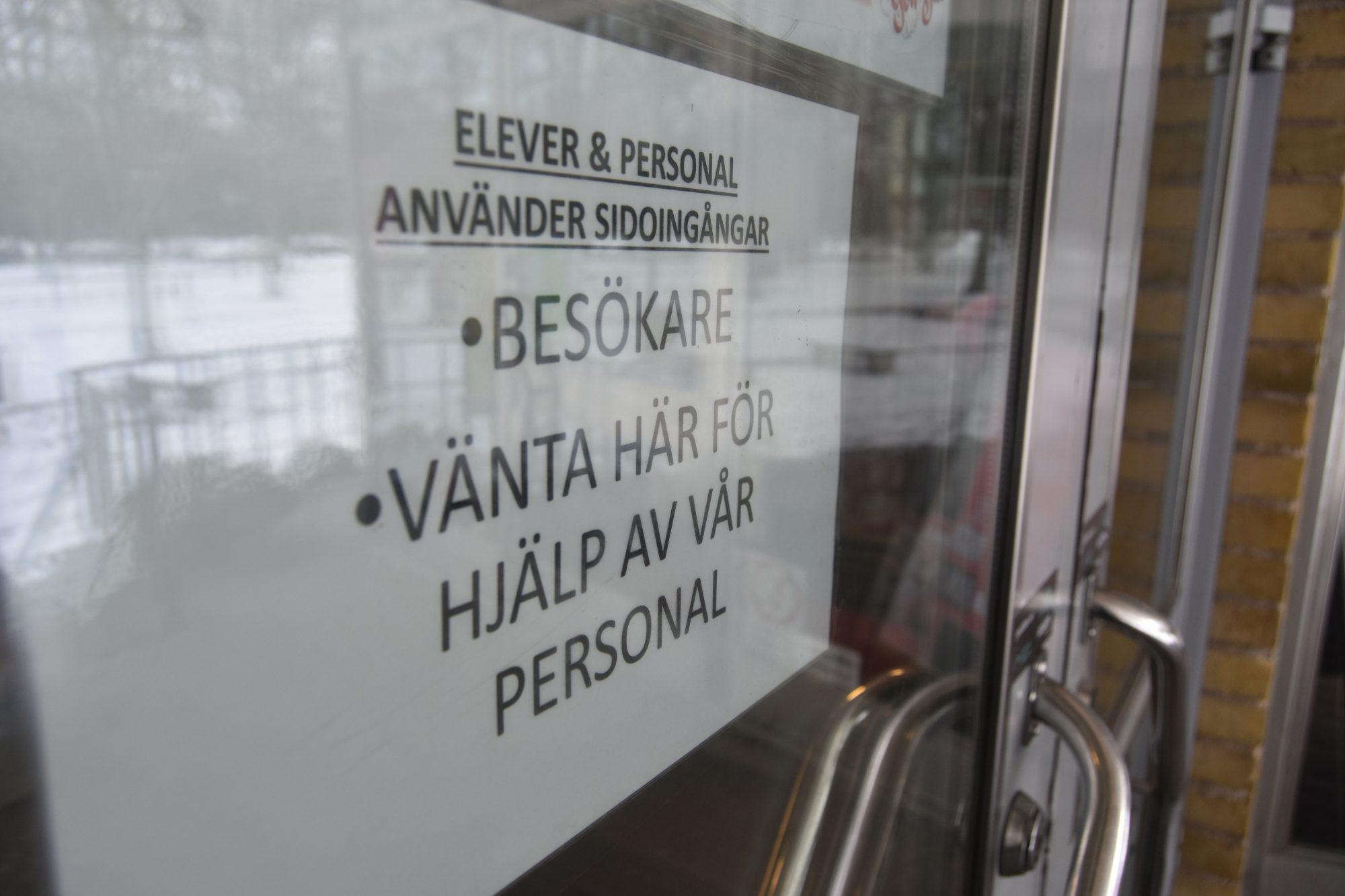 Skylt som uppmanar besökare att invänta personal. Elever och personal hänvisas till sidoingångarna.